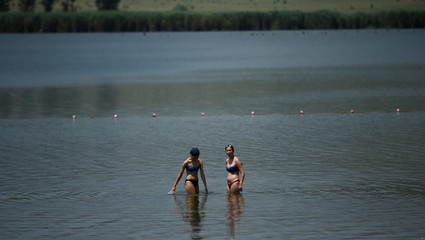 Women cool off in the waters of Lisi lake on a hot summer day in Tbilisi