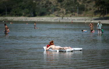 A woman sunbathes in the waters of Lisi lake on a hot summer day in Tbilisi