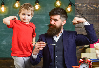 Fatherhood concept. Talented artist spend time with son. Teacher with beard, father and little son having fun in classroom, chalkboard on background. Child cheerful and teacher painting, drawing.