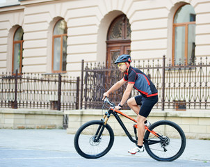 Side view of young sportsman in professional cycling sportswear and helmet riding bicycle near beautiful buildings. Man training, improving hobby, getting ready for contest