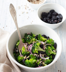 Fresh salad with broccoli, black raisins, red onions, seeds, sesame and flax in a white bowl on a blue wooden background, selective focus. Healthy raw diet salad