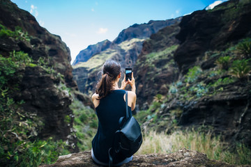 Woman taking photo of mountains landscape using phone