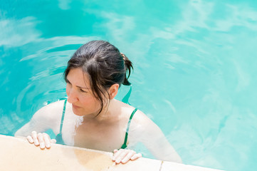 Young brunette woman relaxing in the swimming pool in a resort