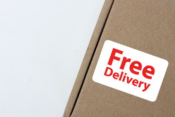 "free delivery, business,online shopping, ecommerce and delivery service concept - brown box with note "" free delivery """