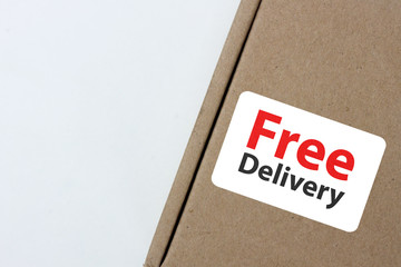 "free delivery, business,online shopping, ecommerce and delivery service concept - brown box with note "" free delivery "" on a gray background."