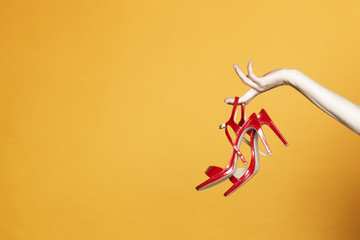 Hand with high hell shoes in studio on yellow background
