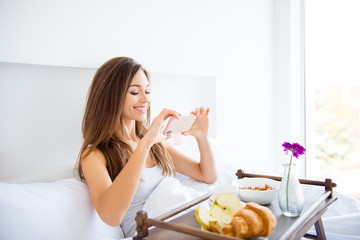 Portrait of cheerful girl having breakfast sitting in bed making photo enjoying idyllic morning in hotel resort