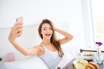 Portrait of cheerful positive girl sitting in bed having breakfast shooting selfie on front camera of smart phone enjoying recreation. Online meeting concept