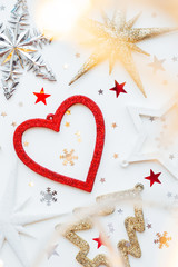 Christmas and New Year background with sparkling fir tree, heart, snowflakes and star confetti. Holiday symbols on white background with light bulbs.