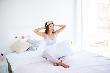 Portrait of cheerful positive girl wake up in good mood sitting on bed enjoying recreation at home