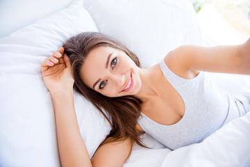Self portrait of cheerful positive girl lying in bed shooting selfie on front camera having online meeting health healthy