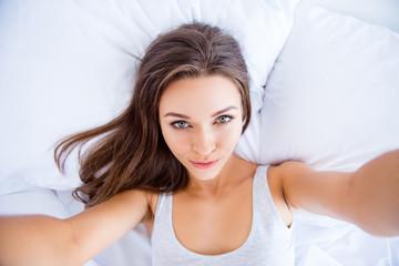 Self portrait of cool sexual girl shooting selfie on front camera having online meeting lying in bed