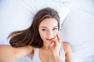 Self portrait of sexual girl lying in bed shooting selfie on front camera enjoying recreation biting finger having online meeting with lover health healthy