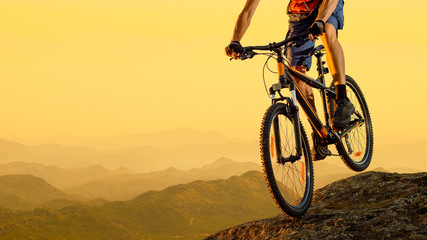Cyclist Riding the Bike Down the Rock at Sunset. Extreme Sport and Enduro Biking Concept.