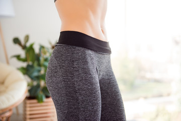 Healthy eating and sport! Cropped close up photo of sexual seductive beautiful attractive flat stomach of woman, wearing tight gray pants leggings tracksuit white background copy-space