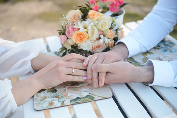 Newlyweds Holding Hands at Table