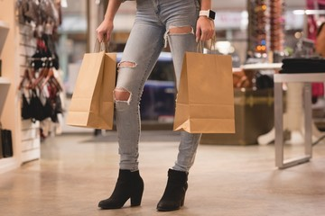 Low section of woman standing with shopping bags
