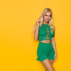 Beautiful Blond Woman In Green Short Jumpsuit Is Looking Away