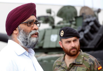 Canada's Defence Minister Harjit Sajjan is pictured next to a Spanish soldier at NATO eFP Canadian-led battlegroup troops in Adazi military base