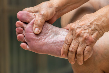 Senior woman's hands massaging her foot, About massage concept