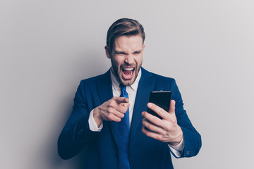 Anger mobilephone mad emotion expressing partner internet people person concept. Portrait of disappointed mad confused with open mouth financier with phone in hand isolated on gray background