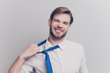 Close up portrait of exhausted frustrated stressed handsome sad unhappy upset entrepreneur trying to take off uncomfortable blue tie formal wear isolated on gray background copy-space Wall mural