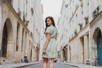 Pretty young woman walking on narrow street