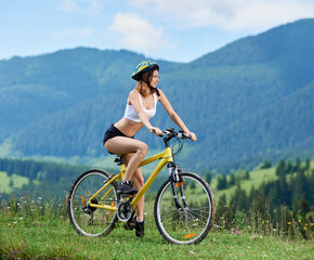 Sporty girl biker riding on yellow bicycle on a rural trail in the mountains, wearing helmet, enjoying valley view. Mountains, forests on the background. Outdoor sport activity lifestyle concept