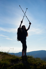 Silhouette of sporty female hiker with backpack standing on the top of a hill, holding her trekking sticks above a head, agains blue sky in the mountains