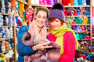 Young women buying colorful pullover in knitwear fashion textile store