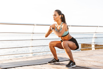 Photo of attractive concentrated woman 20s in tracksuit squatting near sport mat, during workout on boardwalk at seaside