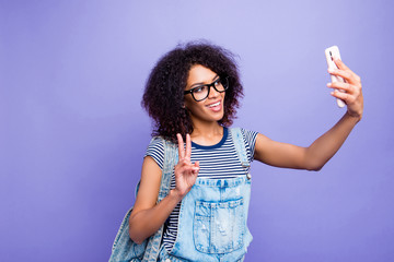 Portrait of trendy cheerful girl in eyeglasses striped outfit shooting selfie on front camera of smart phone gesturing v-sign with two fingers isolated on violent background