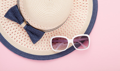 Summer hat with ribbon and sunglasses isolated on colorful background. Top view and copy space.