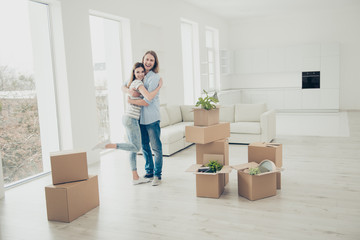 We did it! Rent property happiness furniture concept. Joyful lovely rejoicing beautiful handsome cheerful people in casual denim clothes standing in white spacious room around open boxes with things