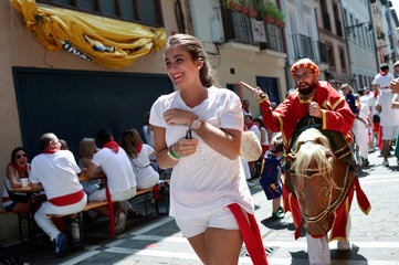 "A woman is chased by a ""Zaldiko"" at the San Fermin festival in Pamplona"