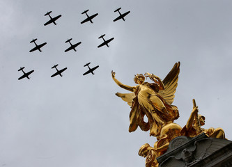 Vintage military aircraft perform a fly past over the Queen Victoria Memorial and Buckingham Palace to mark the centenary of the Royal Air Force in central London