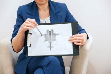 Woman is sitting and pointing on a picture that she is holding in hands. It is attached to tablet. She is using pen to point on hand drawing.