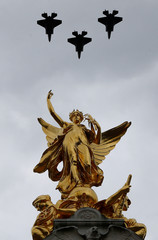 Military aircraft perform a fly past over the Queen Victoria Memorial and Buckingham Palace to mark the centenary of the Royal Air Force in central London