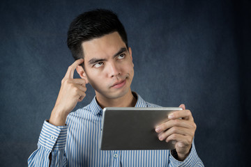 Portrait handsome young asian man wearing a blue  shirt holding smart phone or tablet thinking and looking isolated on gray background. Asian man people.  business success concept..