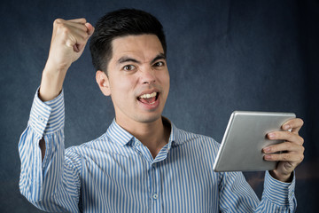Close up handsome young asia man wearing a blue shirt  holding smart phone or tablet excitement or celebrating his victory sign isolated on gray background.