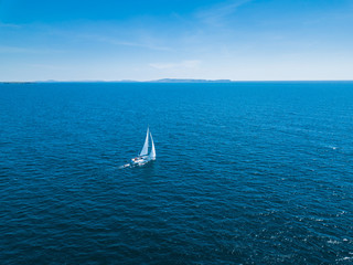 Aerial drone bird's eye view of sail boat cruising in the Aegean deep blue sea