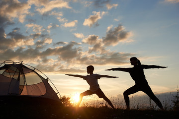 Silhouette view of Yoga Warrior pose exercising by family couple in grass near tent at the daybreak on the background of morning sky with sparse clouds and bright sun. Mom grafts a son's love of sport