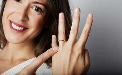 Happy european girl with long dark hair in stylish clothes smiling and holding hand while pointing finger trendy wedding ring over empty white wall background.Copy paste text message space. Close-up