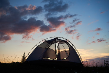 Camping at sunrise in the mountains. The tent stands on the grass with wildflowers under the morning sky with clouds on top of the mountain. The concept of an active lifestyle