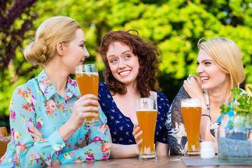 Happy friends toasting with beer in garden pub
