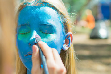 The girl's face is completely painted blue with aqua-grime. Festive preparation.