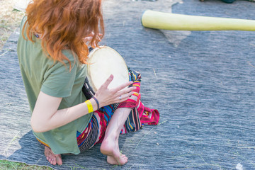 A girl with red hair plays the drum.