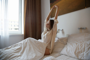 Woman streching in the bed, waking up in the morning,  still sleepy, lazy or tired