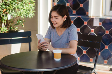 Cheerful asian young woman sitting in cafe drinking coffee and using smartphone for talking, reading and texting. Attractive asian woman holding a cup of coffee while looking on her phone.
