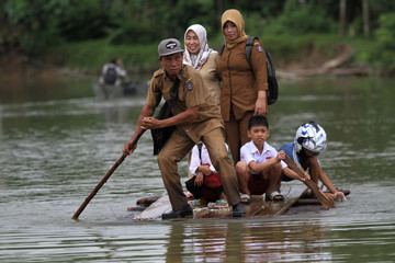 A group of teachers and their student use makeshift raft as they cross the street during flood that hit Ranomeeto Barat village in Konawe Selatan